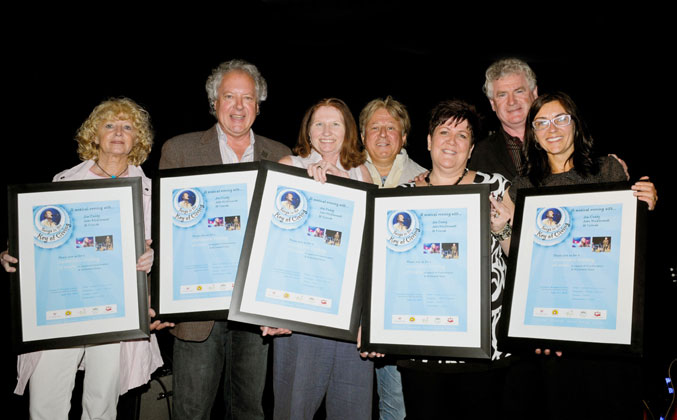 Receiving framed posters for the Songs in the Key of Giving fundraiser are from left: Trudy Eagan (McDermott House Canada), Jan Nichols (Dr. Bob Kemp Hospice), Leslie Hirst (The Carpenter House Hospice), Blair McKeil, Pamela Blackwood (McNally House Hospice), John McDermott and Margaret Jarrell (Hospice Niagara).